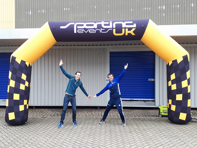 Two men stood under an inflatable race arch