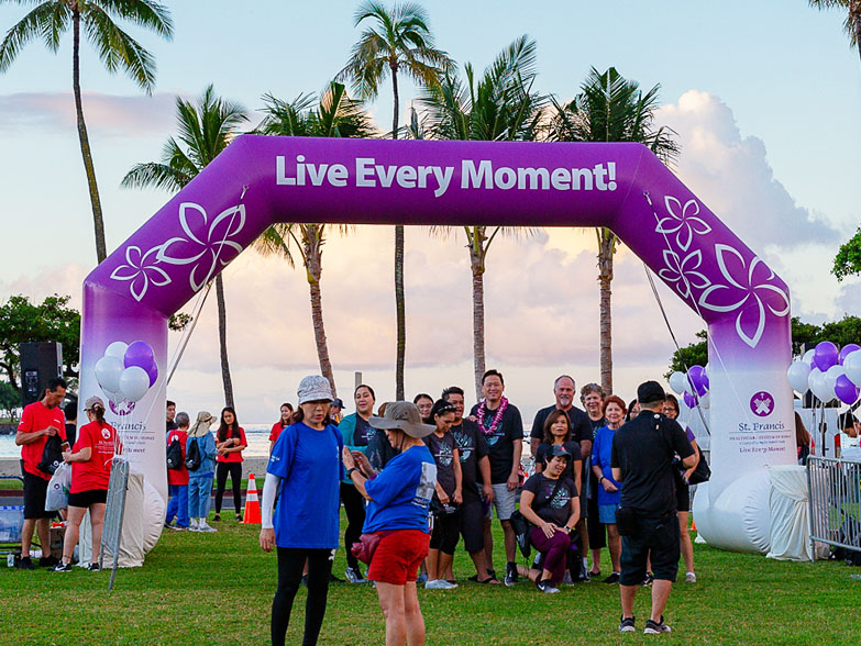 People standing underneath a printed freestanding inflatable race arch